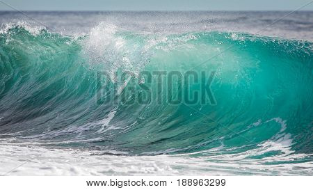 Big turquoise blue wave rolling down to the shore