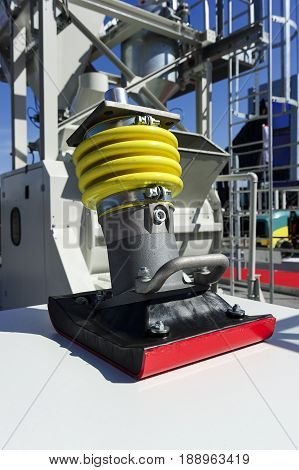 Soil compactor, vibratory rammer machine part, heavy industry, building area with construction equipment and vehicle on blurred background