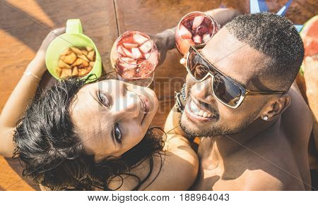 Fashion man and young woman having fun at cocktail bar drinking sangria - Happy multiracial couple at beginning of love story - Funny concept with boyfriend and girlfriend dating on warm retro filter