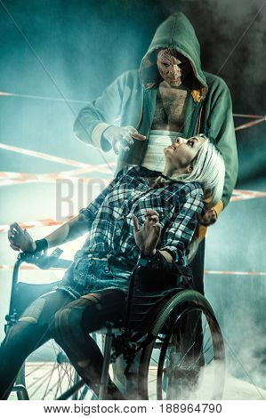 Maniac And His Tied Victim In The Wheelchair On The Dark Background.