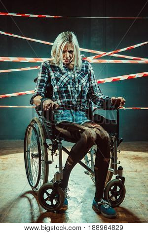 Pretty Woman In The Wheelchair On The Dark Background.
