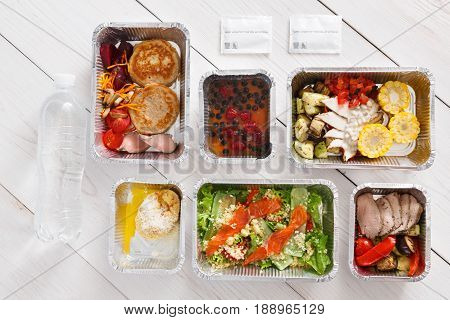 Healthy food delivery, daily ration. Take away of natural organic low carb diet of vegetables, fish and meat. Fitness nutrition in foil boxes. Top view, flat lay with copy space at white wood