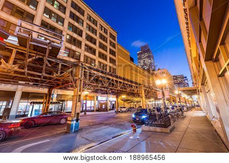 Chicago - March 2017, IL, USA: The street in downtown Chicago at night. Metro ways with passing train and cars moving under them. Wide angle view, long exposure photography