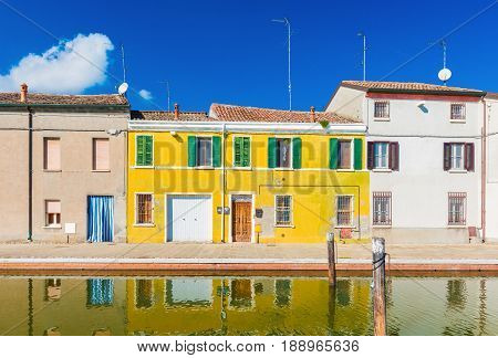 Colored houses reflected in the water. The old street in Comacchio - a small town in the province of Ferrara (Emilia Romagna) also known as