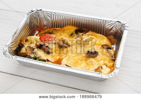 Healthy food delivery in foil, lasagna. Restaurant dishes, lunch for diet