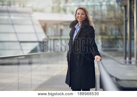 Attractive woman with a lovely friendly smile standing outdoors in a warm dark grey overcoat on an urban concourse with her hand on a railing and copy space