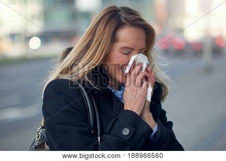 Woman with a seasonal winter cold blowing her nose on a handkerchief or tissue as she walks down an urban street in a health and medical concept