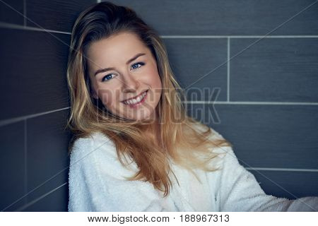 Pretty young blond woman with a happy sincere smile leaning back into the corner on a grey tiled wall with folded arms looking to the side with copy space alongside