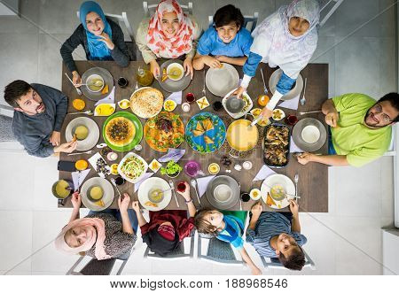 Top view of Muslim family gathering for eating iftar food in Ramadan (looking at camera)