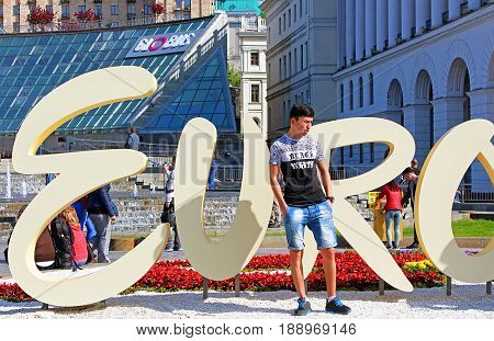 KYIV, UKRAINE - MAY 1, 2017: Unidentified tourist near part of official logo of Eurovision Song Contest 2017 on Maidan Nezalezhnosti (Independence Square)