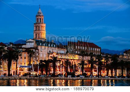 Split, Croatia. View of Split - the second largest city of Croatia at night. Shore of the Adriatic Sea and famous Palace of the Emperor Diocletian with mountains at the background