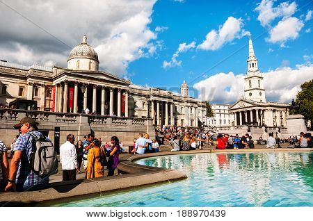 LONDON - AUGUST 31, 2014: Trafalgar square crowded with people in London, UK. It is a popular touristic attraction which commemorates the Battle of Trafalgar and hosts different monuments and statues