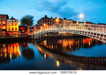 Dublin, Ireland. Night view of famous illuminated Ha Penny Bridge in Dublin, Ireland