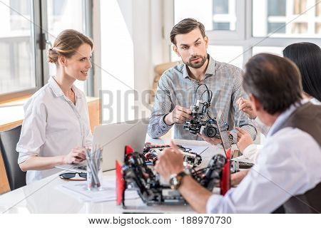 Modern technologies. Pleasant professional engineers sitting at table. Selective focus on young woman with laptop and bearded man holding robot while looking at senior man