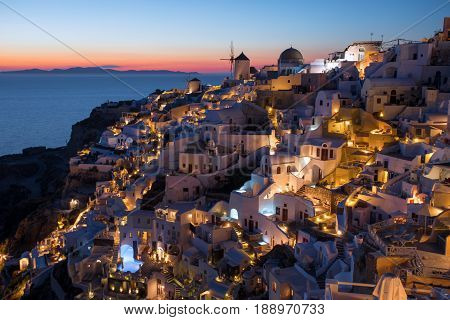 Traditional Oia sunset in Santorini Greece with city lights