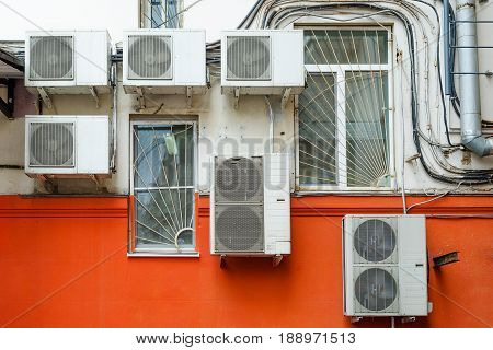 Chaotically located air conditioners on the wall. Element of urban urban landscape. Urban background. Many compressor airs are hanging on a wall