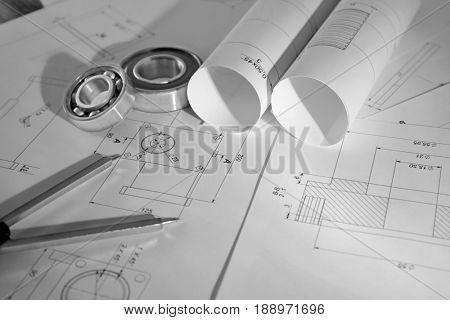 Engineering supplies and part blueprints on workplace