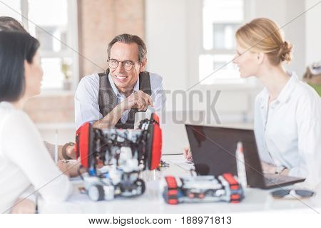 Glad to work with them. Selective focus on pleasant cheerful mature man sitting at the table with his colleagues and smiling while being involved in work