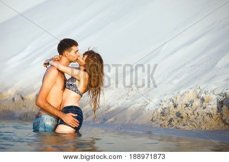 Beach lovers on romantic travel honeymoon vacation summer holidays romance. Young happy girl and man kissing and embracing on water