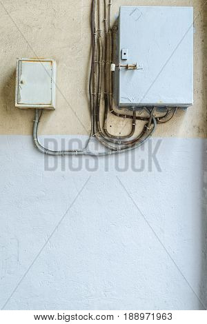 Electrical switchboard on the wall. Wiring to the electrical panel on the wall. Detail of the cityscape. Grey wall