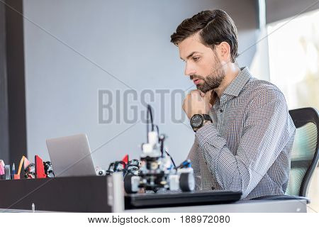 Involved in work. Profile of young bearded man is looking at screen of laptop while touching his chin. Copy space in the left side