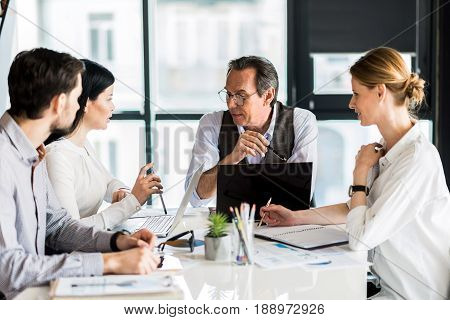 Pleasant work. Involved serious colleagues sitting at table while communicating together. Selective focus on pleasant mature man keeping pencil thoughtfully