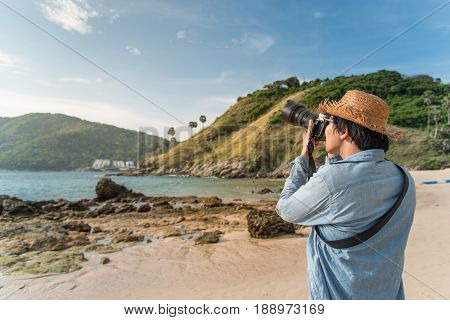 young Asian man photographer with jean shirt and straw hat take photo of tropical island beach and turquoise sea seascape background for summer holiday and vacation travel concepts