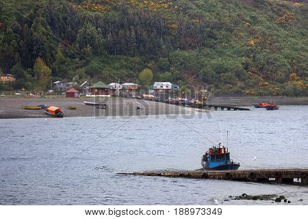 PUERTO MONTT-OCTOBER 17 2014: Fishing boats moored in Angelmo tourist area and restaurant specialists in cooking fish in Puerto Montt, Chile on October 17, 2014