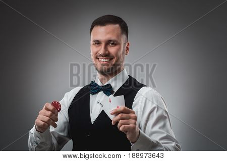 Young man in shirt and waistcoat shows his cards and holds poker chips in his hands, studio shot. Poker. Emotions
