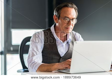 Concentrated on work. Portrait of pleasant serious mature man working on laptop attentively while sitting at table in office