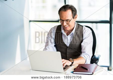 Full concentration at work. Portrait of successful senior man typing on notebook with smile while sitting at table in office