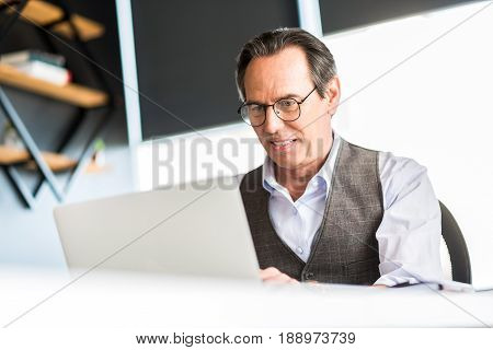 Satisfied with work. Portrait of cheerful mature businessman is looking at screen and typing on laptop while working in office
