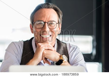 Enjoying working day. Portrait of cheerful senior man is leaning on hands and looking at camera with joy