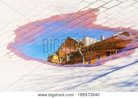Reflection of the roof of the building in the water on the pavement. Cityscape abstract background