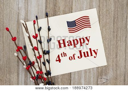 Happy 4th of July text on a greeting card with a red white and blue floral pip berry spray on weathered wood