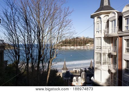 DONOST-DECEMBER 21 2014: On sunny days the people of Donosti take the opportunity to stroll along La Concha Beach in Donosti, Spain on 21 December, 2014
