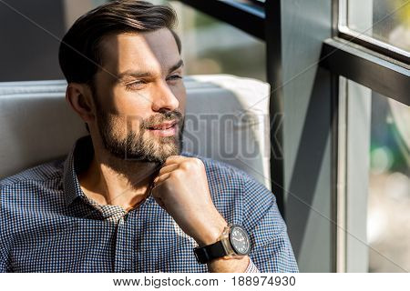 Follow your dreams. Portrait of cheerful bearded young guy is touching his chin while looking through window with slight smile