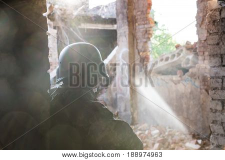 Silhouette Of A Soldier In A Helmet In The Back Light. Military Actions And Assault Of Buildings