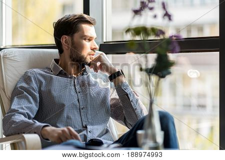 Expectation. Serious young male is sitting in comfortable chair while looking through window thoughtfully