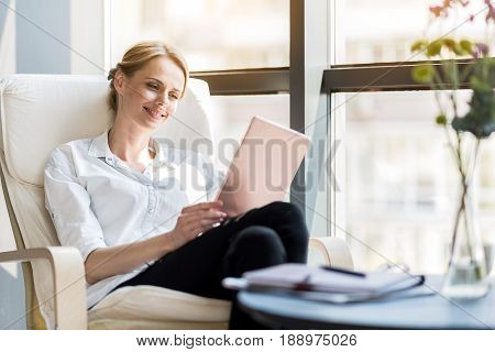 Comfort and pleasure. Elegant positive woman is sitting in big comfortable chair while reading news on tablet
