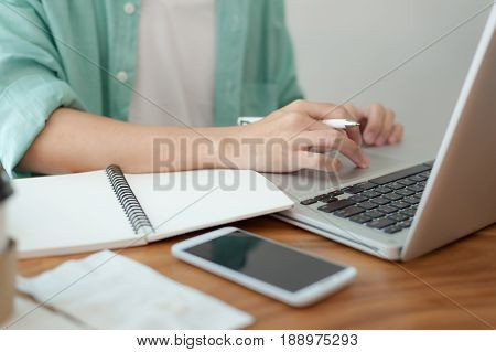 Asian male with casual cloths using laptop computer and internet while working in coffee shop on workday. Freelancer lifestyle and activity concept