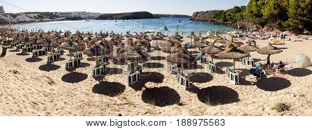 MENORCA-AUGUST 27 2015: Panoramic views of a beach full of people and Sunshades in summer in Menorca, Spain on August 15, 2015