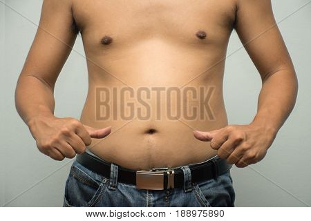 Asian fat man has cholesterol . He shows excess fat of the tummy. By pointing at the his tummy. / Photo concept: fat belly obesity cellulite