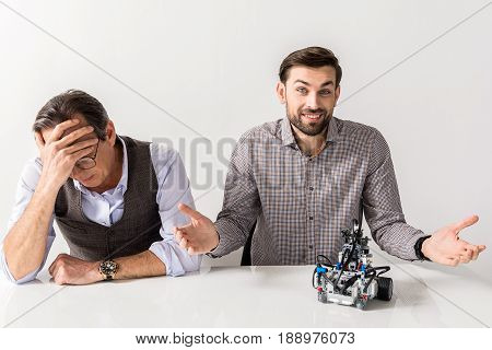Misunderstandings concept. Portrait of disappointed senior man is sitting at table and covering face with hands in deep depression while young bearded guy is expressing helplessness. Isolated