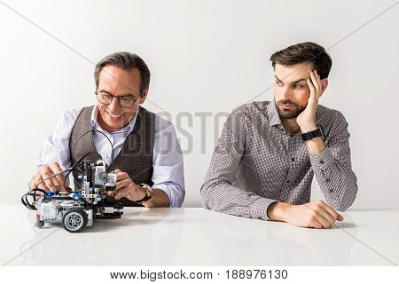 Portrait of joyful mature man is testing robotic toy with smile while young bearded guy is looking at him with dumbfounded. Isolated background