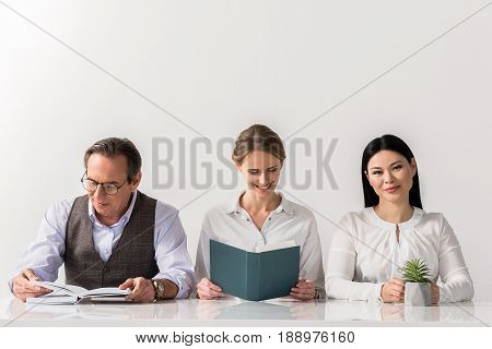 Glad to work together. Portrait of positive woman is sitting at table with flower and looking at camera with joy while her colleagues are reading books with smile. Isolated background