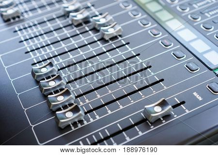 Professional audio mixing console buttons faders and sliders.