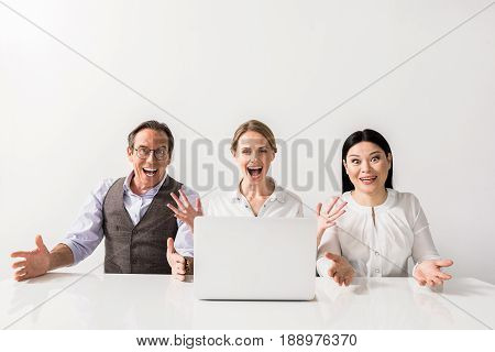 Achievement concept. Portrait of happy positive colleagues are sitting at table with laptop while looking at camera with joy and gesturing with glee. Isolated background