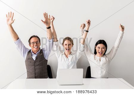 Concept success in work. Portrait of jubilant energetic team is sitting at table and holding hands up while expressing happiness and gladness. Isolated
