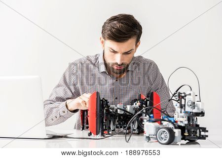 Smart device. Portrait of concentrated professional employee is testing functions of robot. Isolated background